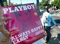 A vendor shows Indonesian version of Playboy magazine to passing motorists as a Muslim woman walks past by on a street in Jakarta, 7 April 2006 (photo: AP)