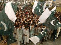 Pakistanische junge Männer schwenken am Unabhängigkeitstag die Nationalflagge; Foto: AP