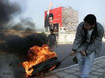 Hizbollah-Anhänger mit brennenden Reifen vor Plakat mit Hassan Nasrallah; Foto: AP