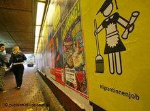 Passanten schauen in einer Tunnelunterführung auf ein Plakat mit einem Piktogramm von Migrantas; Foto: dpa