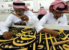 Saudi-arabische Männer weben Koran-Verse in ein Tuch; Foto: dpa