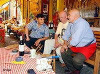 Inhaber und Gäste sitzen vor einem Spezialitätengeschäft in Berlin-Kreuzberg; Foto: dpa