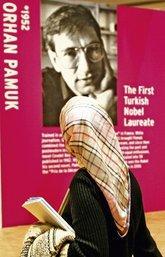 Frau mit Kopftuch vor Plakat von Orhan Pamuk auf der Frankfurter Buchmesse
