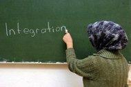 A Muslim woman writes the word integration on a blackboard (photo: dpa)