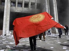 Demonstranten mit Nationalfahne Kirgistans stürmen den Regierungssitz in Bischkek; Foto: AP