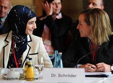 Bundesfamilienministerin Kristina Schröder auf der Islamkonferenz im Gespräch mit einer Muslima; Foto: dpa