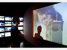 Mann beobachtet die Ereignisse vom 11. September auf einer Leinwand; Foto: dpa