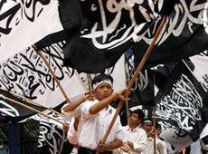 Indonesische Jugendliche von der islamistischen Gruppierung Hizbut Tahrir schwenken Fahnen mit islamischer Schrift; Foto: AP
