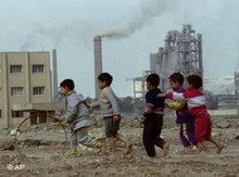 Spielende Kinder in der Nähe eines Industriekomplexes; Foto: AP