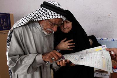 A man and woman study a ballot sheet during the Iraqi parliamentary election (photo: AP)