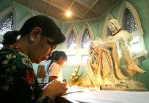A woman prays at an altar during church services in Medan, Indonesia (photo: AP)