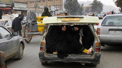 Eine Frau versteckt sich im Kofferraum eines Autos; Foto: DW
