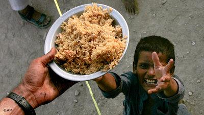 Pakistanischer Junge streckt die Hände zu einem Teller Essen hoch; Foto: AP