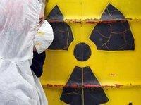 Mann in Schutzkleidung vor Fass mit radioaktivem Inhalt; Foto: dpa