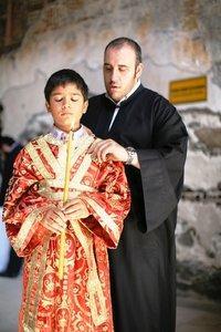 Junge mit Kerze und orthodoxer Priester bei der Zeremonie; Foto: Iason Athanasiadis