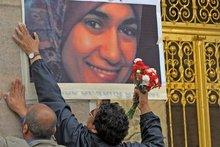 Zwei Männer befestigen ein Bild von dem Mordopfer Marwa al-Sherbiny an eine Wand; Foto: dpa