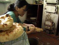Zhainagul bäckt Brot für ihre Tochter; Foto: Edda Schlager