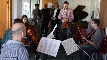 Martin Kögel vom Deutschen Symphonie Orchester Berlin mit Schülern im Westjordanland; Foto: Mustafa Khadeisa/DW