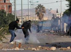 Jugendliche Demonstranten werfen Steine gegen Sicherheitskräfte in der Provinzstadt Regueb, nahe Sidi Bouzid; Foto: AP