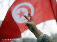 Demonstrant in Tunis formt die Hand zum Victory-Zeichen vor einer tunesischen Fahne; Foto: dpa