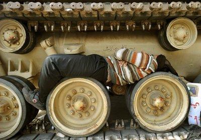 Demonstrant auf dem Tahrir-Platz schläft in Panzerrädern; Foto: dpa