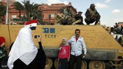 Demonstranten auf dem Tahrir-Platz machen Fotos von einem Panzer nach Mubaraks Rücktritt; Foto: AP