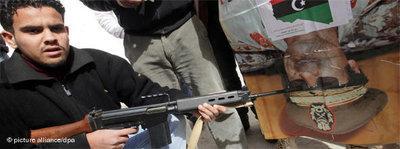 Libyer hält eine Waffe an ein Gaddafi-Poster; Foto: dpa