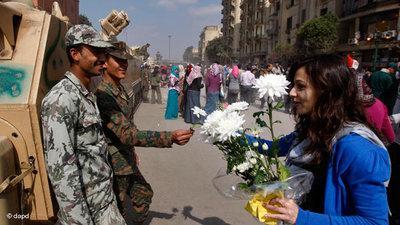 Ägypterin überreicht Blumen an zwei Soldaten auf dem Tahrir-Platz in Kairo; Foto: dapd