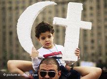 Ägyptischer Demonstrant mit Kind, das ein Halbmond und ein Kreuz aus Styropor trägt; Foto: dpa