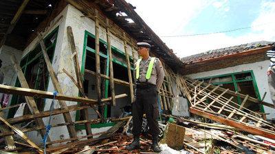 Ein Polizist steht vor dem zerstörten Haus eines Ahmadiyah-Mitglieds in Pandeglang; Foto: AP