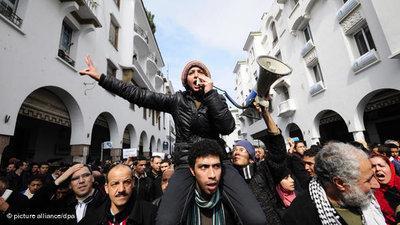 Junge Frau mit Lautprecher und Protestierende bei einer Anti-Regime-Demonstration in Rabat im Februar; Foto: dpa
