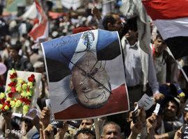 Demonstranten halten ein Plakat mit einem durchgestrichenen Foto von Ali Abdullah Saleh hoch; Foto: dapd