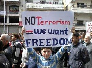 "Boy holding up a sign that reads ""No Terrorism. We want Freedom"" (photo: AP)"