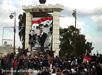 Demonstranten zerstören ein Plakat mit dem Porträt Baschar al-Assads in Daraa; Foto: picture alliance/abaca