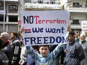 Ein Junge hält bei einer Anti-Regierungsdemonstration in Banias ein Plakat, auf dem steht: 'We want Freedom, no Terrorism'; Foto: AP