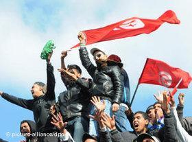 Protestierende Jugendliche schwenken Tunesien-Fahne; Foto: dpa