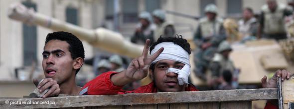 Junger Mann macht auf dem Tahrir-Platz das Victory-Zeichen; Foto: dpa