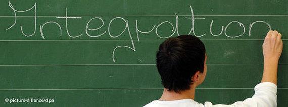 Schüler schreibt das Wort Integration auf eine Tafel; Foto: dpa