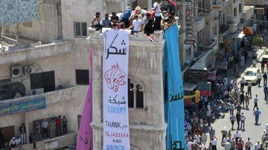 Einwohner der von Assads Truppen belagerten Stadt Hama bedanken sich auf einem Spruchband für die Berichterstattung von Al-Jazeera und Shaam News Network; Foto: AP