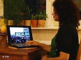 Bloggerin schaut sich am Laptop ein Video von Demonstrantionen in Tunesien an; Foto: DW