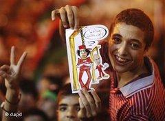 Libysches Kind hält Karikatur hoch, das Muammar al-Gaddafi und dessen Sohn Seif al-Islam am Galgen zeigt; Foto: dapd