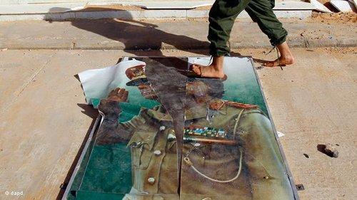 Mann läuft über zerrissenes Gaddafi-Plakat in Tripolis; Foto: dapd
