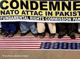 Pakistaner in Hyderabad treten auf die Amerikanische Flagge und demonstieren mit einem Plakat gegen den Nato-Luftangriff; Foto: dpa