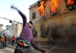 Jugendliche Demonstranten vor brennendem Gebäude am Tahrir-Platz; Foto: AP
