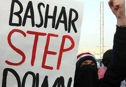 A demonstrator with a placard that reads 'Bashar step down' (photo: dpa)