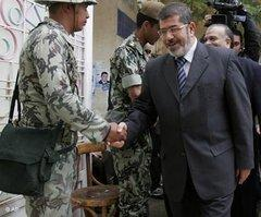 Mohammed Morsi, Sprecher der Muslimbruderschaft, schüttelt einem Soldaten die Hand; Foto: AP