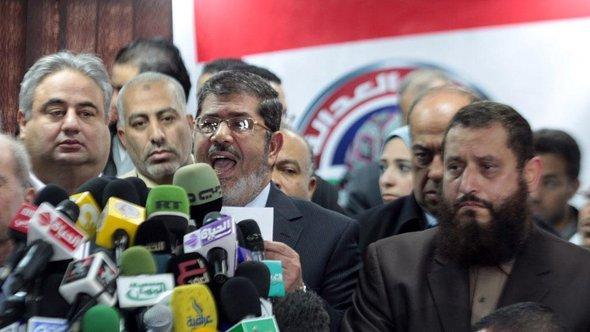 Der Präsident der ägyptischen Muslimbrüder-Partei, Mohammed Morsy, spricht nach dem Wahlsieg vor der Presse; Foto: dpa