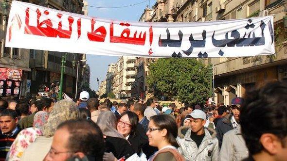 """Plakat mit der Aufschrift """"Das Volk will den Sturz des Regimes""""; Foto:"""
