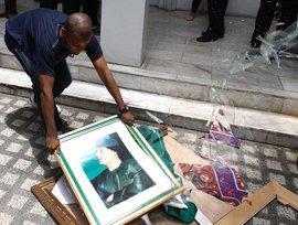 Anhänger der Rebellen zerschlägt Bild Gaddafis; Foto: picture-alliance