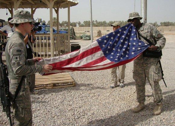 US-Soldaten im Irak falten die amerikanische Flagge auf ihrer Militärbasis im Irak zusammen; Foto: dpa